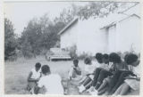 Photograph, students sitting outside of Freedom School engaged in their studies