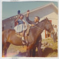 Photograph, little girl sitting on horse and adult male holding reigns of horse