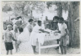 Photograph, Mississippi residents gathered around table  outside with food
