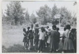 Photograph, Carole Gross in field with children in Mississippi